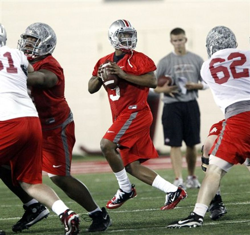 In this photo taken March 31, 2011, Ohio State quarterback Taylor Graham (19) throws a pass to Carlos Hyde (34) during the first day of spring NCAA college football practice in Columbus, Ohio. With three-year starter Terrelle Pryor sidelined for the spring  after surgery and also facing a five-game suspension this fall, the Buckeyes are looking at four candidates to take his spot until he plays in his first game in October. Joe Bauserman, Kenny Guiton, Taylor Graham and Braxton Miller are sharing the snaps during spring workouts. (AP Photo/Terry Gilliam)