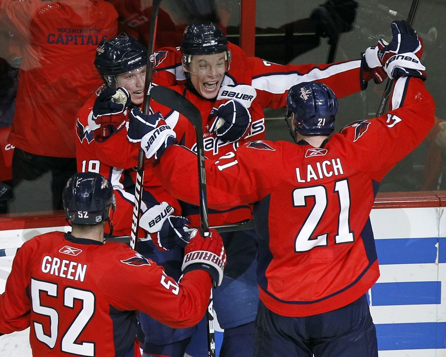 Washington Capitals Mike Green (52), Brooks Laich (21) and Nicklas Backstrom (19), from Sweden, celebrate the game-winning goal by Alexander Semin, top right, from Russia, in the overtime period of Game 1 of a first-round NHL hockey playoff series with the New York Rangers, Wednesday, April 13, 2011, in Washington. The Capitals won 2-1.(AP Photo/Alex Brandon)