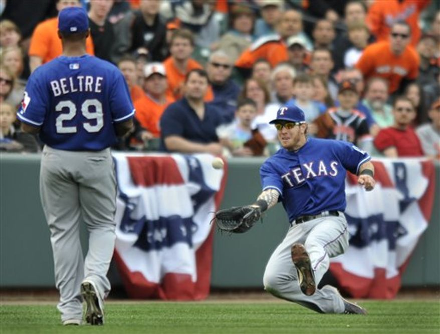 Texas Rangers left fielder Josh Hamilton, right, slides and catches a foul ball hit by Baltimore Orioles' Matt Wieters as third baseman Adrian Beltre  (29) looks on during the ninth inning of a baseball game on Sunday, April 10, 2011, in Baltimore. The Rangers won 3-0. (AP Photo/Gail Burton)