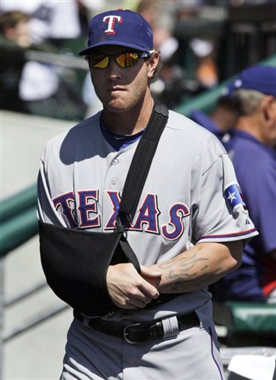 Texas Rangers' Josh Hamilton sits in the dugout with his right arm in a sling during the first inning of a baseball game against the Detroit Tigers in Detroit, Wednesday, April 13, 2011. The Rangers put Hamilton on the 15-day disabled list Wednesday after breaking his upper right arm on a headfirst dive into home plate the day before against the the Tigers. He is expected to miss six to eight weeks.  (AP Photo/Paul Sancya)