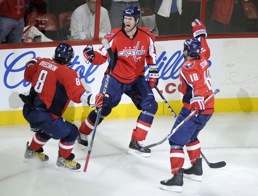 Washington Capitals center Jason Arnott, center, celebrates his goal with Alex Ovechkin (8), of Russia, and Marco Sturm (18), of Germany, during the second period in Game 2 of a first-round NHL hockey playoff series on Friday, April 15, 2011, in Washington. (AP Photo/Nick Wass)