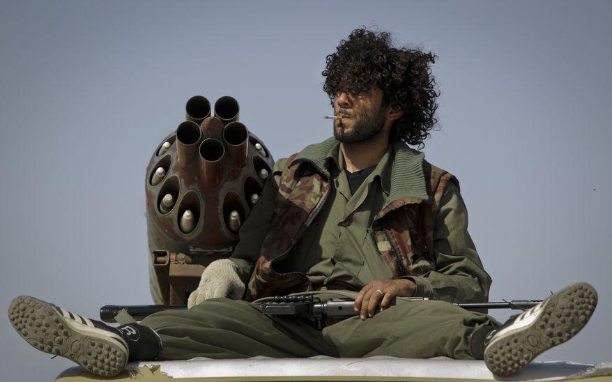 A Libyan rebel fighter smokes a cigarette next to a multiple rocket launcher in the back of a pickup truck, as the rebels prepare to make an advance, in the desert on the outskirts of Ajdabiya, Libya. (AP Photo/Ben Curtis)