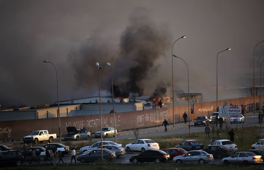 Fire and smoke rises from storage warehouse at a construction site that is run by a foreign company, with no clear causes of the incident, in Benghazi, Libya Friday, April 15, 2011. (AP Photo/Nasser Nasser)