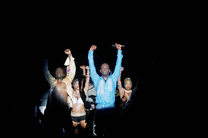 """Hundreds of devoted fans gathered under the breeze of spinning ceiling fans in a steamy warehouse-like club to see the opening night performance of """"Fela!"""" in Nigeria with Sahr Ngaujah, in blue shirt, in the title role. (Associated Press)"""