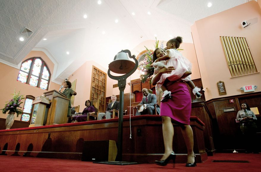 Yolanda King, 3, the only grandchild of the Rev. Martin Luther King Jr., and her mother, Arndrea King, rang a liberty bell at Friday's re-opening ceremony for the restored sanctuary at historic Ebenezer Baptist Church in Atlanta. (Associated Press)