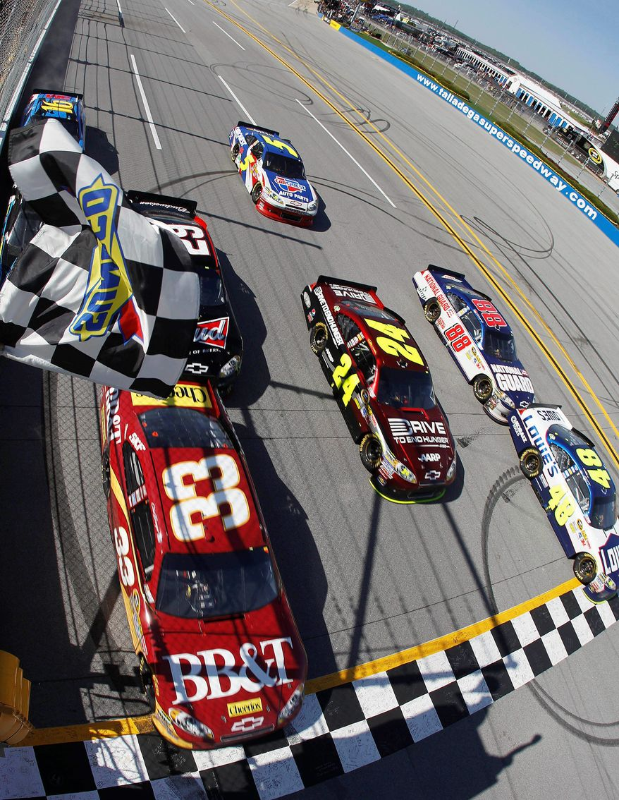Jimmie Johnson (48) crosses the finish line 0.002 seconds ahead of Clint Bowyer (33) to win the NASCAR Sprint Cup Series race Sunday at Talladega Superspeedway, tying for the closest finish ever. (Associated Press)