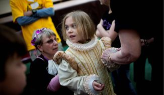 Anais Buron, 7, of Bethesda, tries on a Renaissance-era dress during Sunday's open house at the Folger Shakespeare Library celebrating Shakespeare's 446th birthday. The costumes were among the activites tied to the English author's life and times. Jester and entertainer Nick Newlin (below)j uggles for visitors at Shakespeare's birthday celebration. (Drew Angerer/The Washington Times)