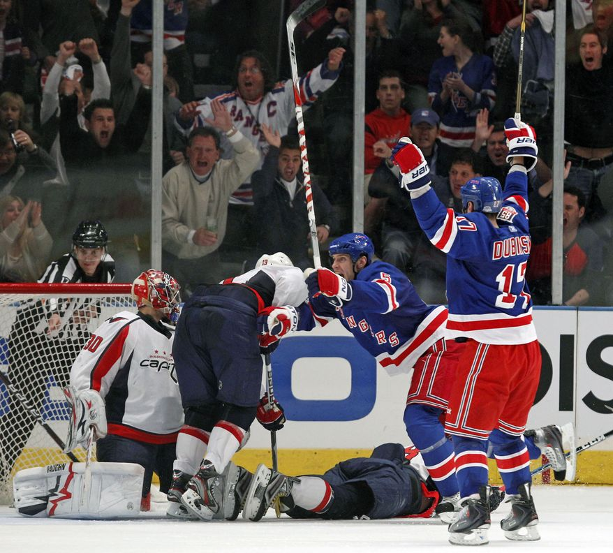 New York Rangers defenseman Dan Girardi (5) and left wing Brandon Dubinsky (17) celebrate Dubinsky's game-winning goal against the Washington Capitals in the final minutes of the third period of Game 3 of their first-round NHL hockey Stanley Cup playoff series at Madison Square Garden in New York, Sunday, April 17, 2011. Capitals goalie Michal Neuvirth (30) watches as Capitals left wing Alex Ovechkin (8) lies on the ice. The Rangers won 3-2. (AP Photo/Kathy Willens)