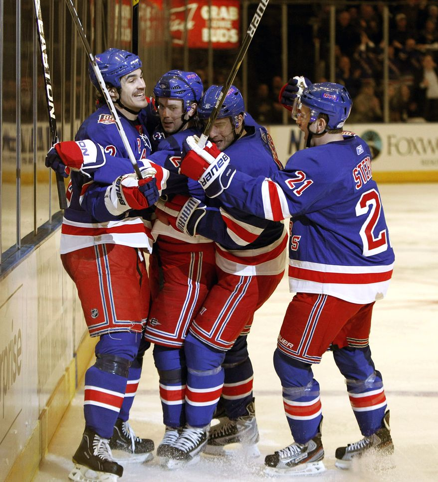 New York Rangers center Brian Boyle, left, left wing Wojtek Wolski, second from right, and center Derek Stepan, (21) celebrate with center Erik Christensen, second from left, after Christensen scored against the Washington Capitals in the second period of Game 3 of a first-round NHL hockey Stanley Cup playoff series at Madison Square Garden in New York, Sunday, April 17, 2011. (AP Photo/Kathy Willens)