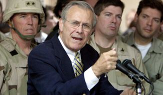** FILE ** Former Defense Secretary Donald H. Rumsfeld, here in 2004 with U.S. troops in Iraq. (Associated Press)