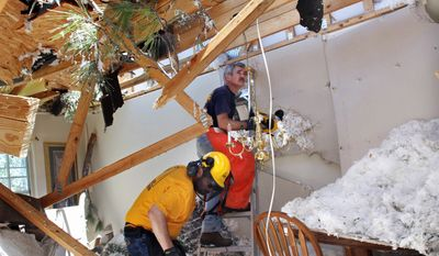 Glen Passner (front) and Craig Ownes, volunteers with N.C. Baptist Men, examine damage in Raleigh, N.C., on Sunday. A pine tree cut through the upper level of the house. (Associated Press)