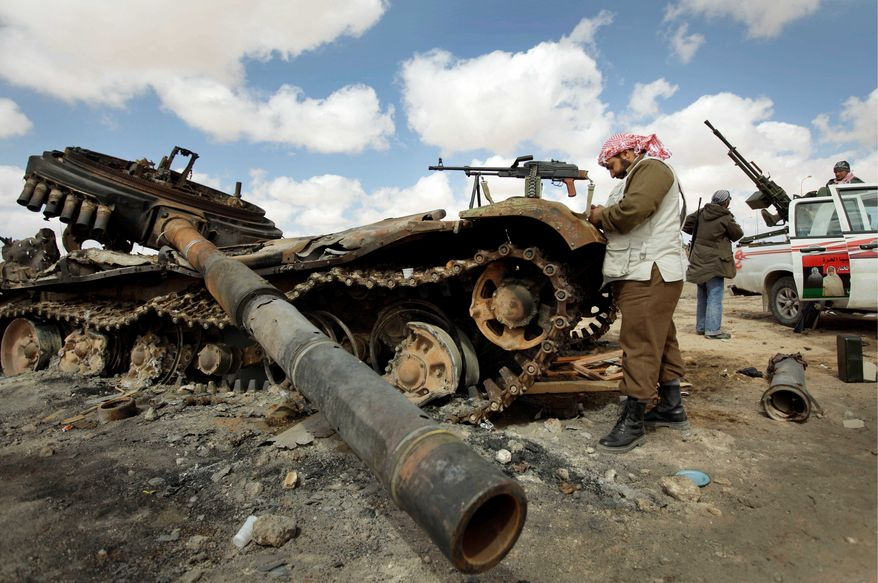 A Libyan rebel fighter reads his Koran next to a tank of the pro-Gadhafi forces that was destroyed near Ajdabiya, Libya. The loyal forces have changed their tactics since NATO airstrikes began. (Associated Press)