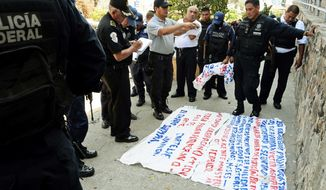 "Police examine a ""narco-manta,"" a warning message painted on a banner left near the site where five dismembered bodies were found on the sidewalk next to a car in Acapulco. (Associated Press)"