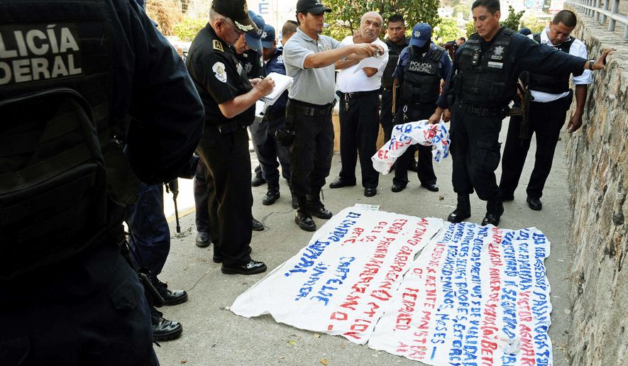 """Police examine a """"narco-manta,"""" a warning message painted on a banner left near the site where five dismembered bodies were found on the sidewalk next to a car in Acapulco. (Associated Press)"""