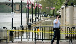 A U.S. Park Police officer keeps watch as the rising water of the Potomac River floods the Georgetown waterfront Monday morning. (Rod Lamkey Jr./The Washington Times)