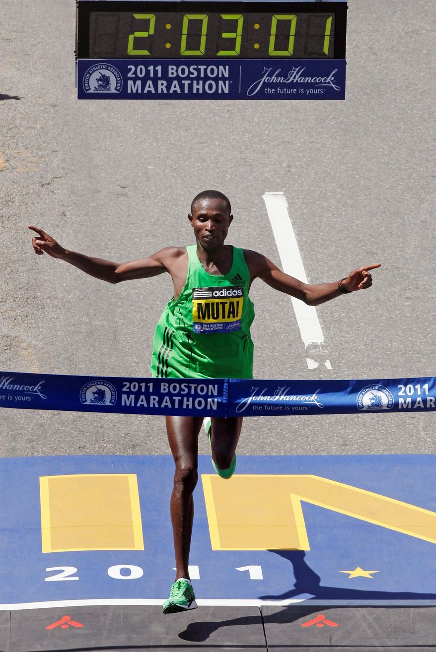 ASSOCIATED PRESS PHOTOGRAPHS Geoffrey Mutai of Kenya takes the final strides of the fastest marathon ever run in the men's division of the 115th Boston Marathon. Strong winds helped Mutai post a time of 2:03.02.