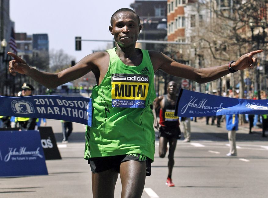 Winner Geoffrey Mutai of Kenya crosses the finish line of the 115th Boston Marathon in Boston Monday, April 18, 2011. (AP Photo/Elise Amendola)