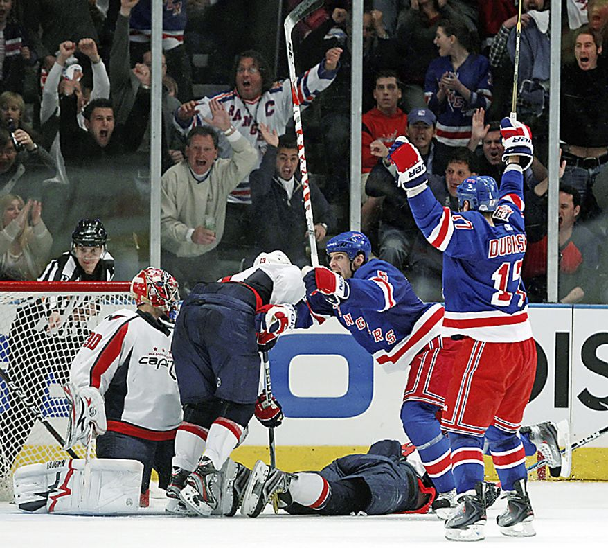 New York Rangers defenseman Dan Girardi (5) and left wing Brandon Dubinsky (17) celebrate Dubinsky's game-winning goal against the Washington Capitals in the final minutes of the third period of Game 3 of their first-round NHL Stanley Cup playoff series at Madison Square Garden in New York, Sunday, April 17, 2011. Capitals goalie Michal Neuvirth (30) watches as Capitals left wing Alex Ovechkin (8) lies on the ice. The Rangers won 3-2. (AP Photo/Kathy Willens)