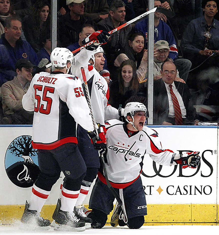 Washington Capitals defenseman Jeff Schultz (55) and Mike Knuble (center) celebrate with teammate Alex Ovechkin (right) in the second period of Game 3 of a first-round NHL Stanley Cup playoff series at Madison Square Garden in New York, Sunday, April 17, 2011. (AP Photo/Kathy Willens)