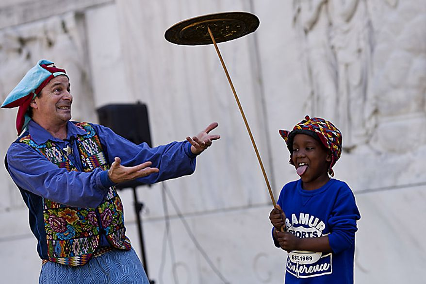 Christopher Hart, 8, of the District, holds a spinning plate as jester and entertainer Nick Newlin looks on during an open house for Shakespeare's Birthday at the Folger Shakespeare Library, in Washington, D.C., Sunday, April 17, 2011. (Drew Angerer/The Washington Times)