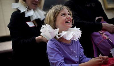 "Lark Goodson,7, of the District, gets help from volunteer Heidi Keller as she puts on a Renaissance era ""ruff"" she made during an open house for Shakespeare's Birthday at the Folger Shakespeare Library, in Washington, D.C., Sunday, April 17, 2011. Ruffs were popular in the 1580s to 1590s. (Drew Angerer/The Washington Times)"