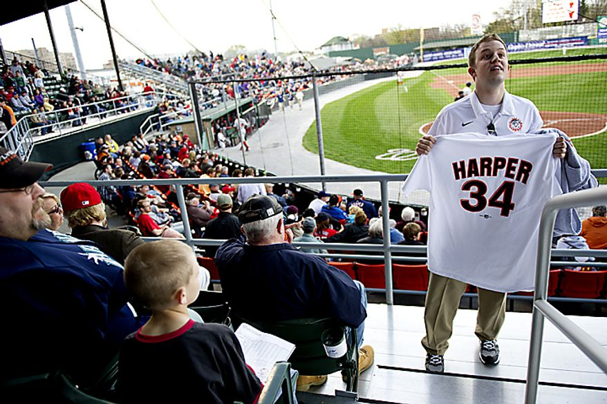 """Jeff Lamparski sells Bryce Harper T-shirt jerseys in the stands during the Hagerstown Suns' home opener against the Lakewood Blueclaws at Municipal Stadium in Hagerstown, Md., on Friday, April 15, 2011. """"This weekend will be the biggest sales weekend ever for us,"""" Lamparski said. (Drew Angerer/The Washington Times)"""