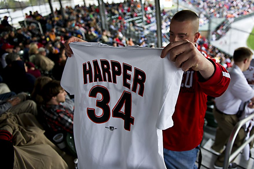 "Timothy Draper of Hagerstown, Md., walks back to his seat as he shows his family his new Bryce Harper T-shirt jersey during the Hagerstown Suns' home opener against the Lakewood Blueclaws at Municipal Stadium in Hagerstown, Md., on Friday, April 15, 2011. ""It's good to have him here, but I doubt he'll be here very long,"" Draper said. (Drew Angerer/The Washington Times)"