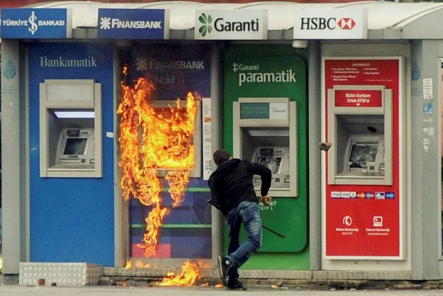 A protester attacks ATMs amid a clash in Istanbul on Tuesday between Kurdish demonstrators and Turkish police. The main Kurdish party threatened to boycott Turkey's upcoming election because some Kurdish candidates will be barred. (Associated Press)