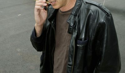Commercial pilot Bill Phillips, using his cellphone on the tarmac at North Little Rock Municipal Airport in Arkansas, is part of a trend of people abandoning landline phones in favor of cellphones. (Associated Press)