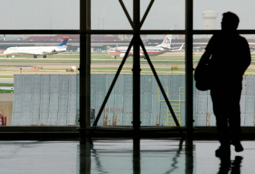 ** FILE ** A traveler waits in Terminal C at Dallas-Fort Worth International Airport in 2008 as passenger jets taxi nearby. (Associated Press)