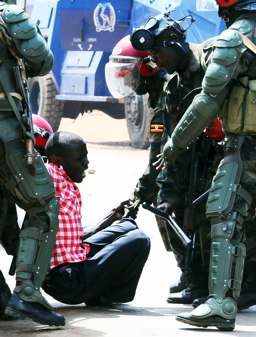 """Ugandan military police arrest a demonstrator during Monday's """"walk to work"""" protest against the high cost of fuel and food in Kampala. The same day, police arrested Kizza Besigye, the country's top opposition leader, for the third time in a week. Mr. Besigye and about a dozen members of parliament were arrested while they were trying to walk to work. (Associated Press)"""