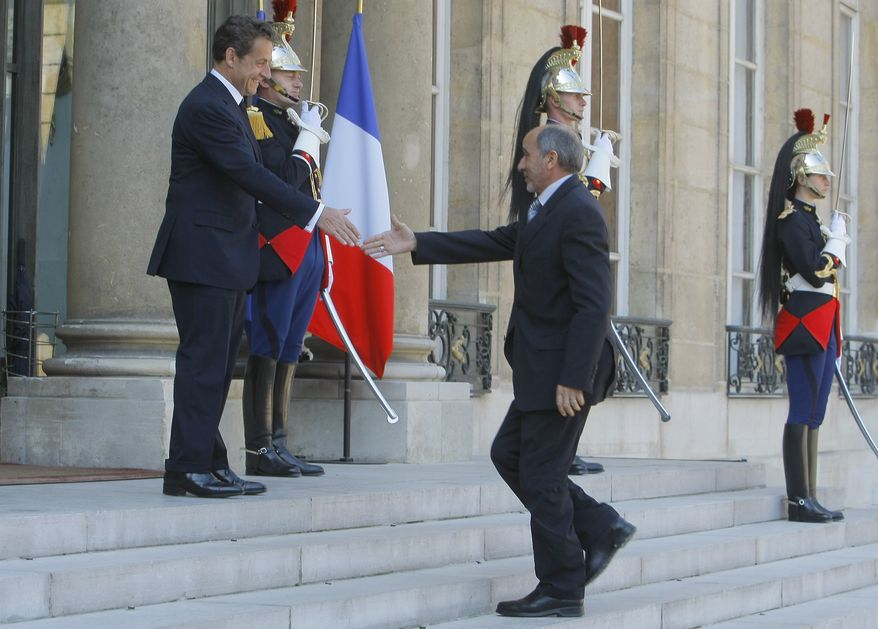 France's President Nicolas Sarkozy, left, welcomes Libyan National Transitional Council's Mustapha Abdeljalil at the Elysee Palace in Paris, France, Wednesday, April 20, 2011. France's government said Wednesday it will send a small number of military liaison officers to Libya to work with opposition forces, but no ground troops. (AP Photo/Jacques Brinon)