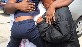 Evette Davis hugs daughter Heaven, 5, and son Julian, 9, after a shooting at Ross Elementary School in Houston on Tuesday, April 19, 2011. A kindergartner who brought a loaded gun to the school Tuesday was among three students injured by fragments when it fired after falling from his pocket as he sat down for lunch, officials said.  (AP Photo/Houston Chronicle, James Nielsen)
