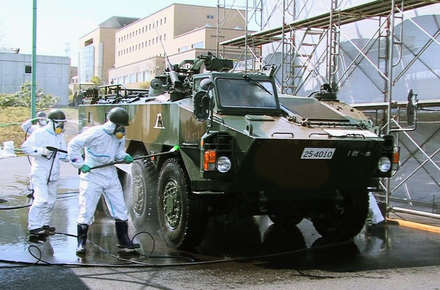 ** FILE ** In this April 12, 2011, photo released by the Japan Defense Agency via Kyodo News, Japanese soldiers wash an armored vehicle to remove potential radiation contamination at J-Village, a soccer training complex. The sports complex is about about 20 kilometers (12 miles) from the crippled Fukushima Dai-ichi nuclear plant. (AP Photo/Japan Defense Agency via Kyodo News)