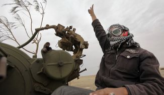 A Libyan rebel fighter manning an anti-aircraft gun flashes the victory sign Wednesday as his vehicle advances towards the front line, on the outskirts of Ajdabiya, Libya. Moammar Gadhafi's loyalists shelled the Nafusa mountain area and clashed with opposition forces in the besieged coastal city of Misrata on Wednesday, rebels said, as the Libyan leader also sought to quell resistance in the western part of the country that is largely under his control. (Associated Press)