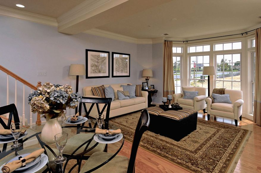 The Picasso model, an upper-level home in the stacked town-home-style condominium community at the Villages of Urbana, has a living room and dining room at the front of the main level.