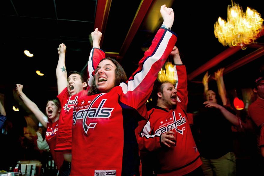 "CHEERING: Jenn Rubenstein of Arlington celebrates the Capitals' double-overtime victory Wednesday at Union Jack's in Arlington. ""Everybody in town is rooting for the team; everybody in the community is involved,"" fan Chris Koves said. ""As long as you have youth and excitement, this team is going to get a lot of hockey converts."" (Drew Angerer/The Washington Times)"