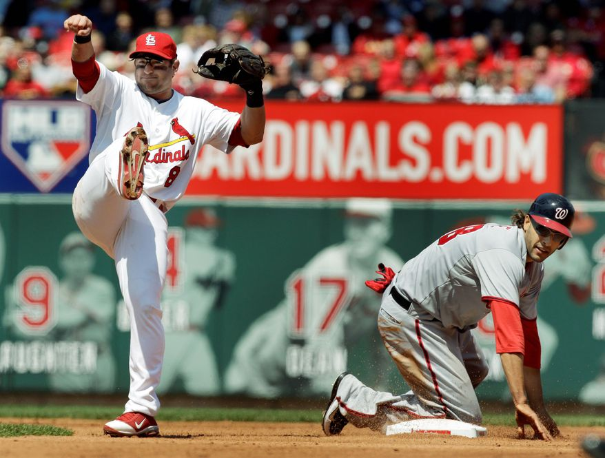 St. Louis Cardinals second baseman Nick Punto (left) turns a double play as Washington Nationals' Michael Morse is out at second base during the fifth inning. (Associated Press)