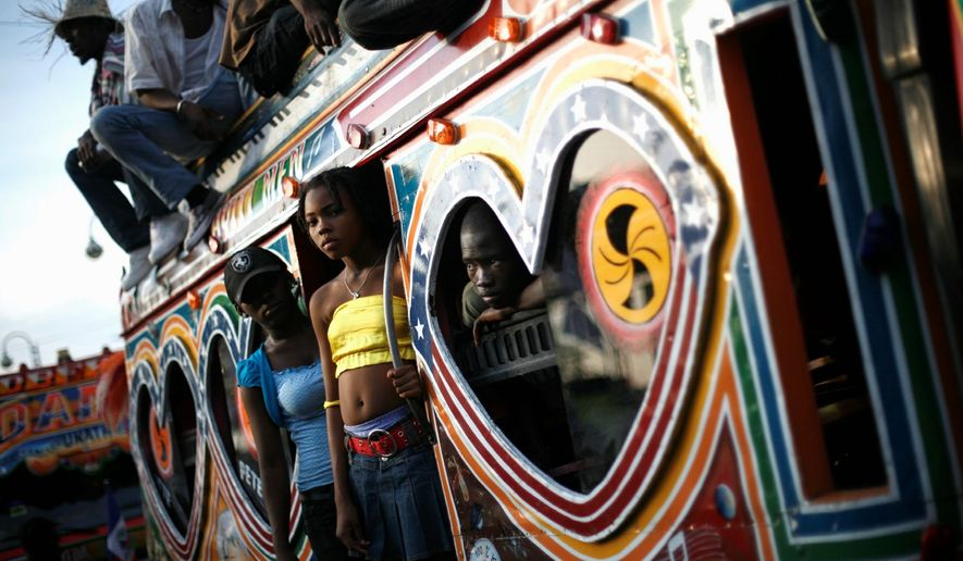 "Haitians aboard a bus called a ""tap tap"" observe a Carnival parade in Port-au-Prince, Haiti, in February 2009. Along the side of one such bus is a painted shrine to T.I., an American rapper. (Associated Press)"