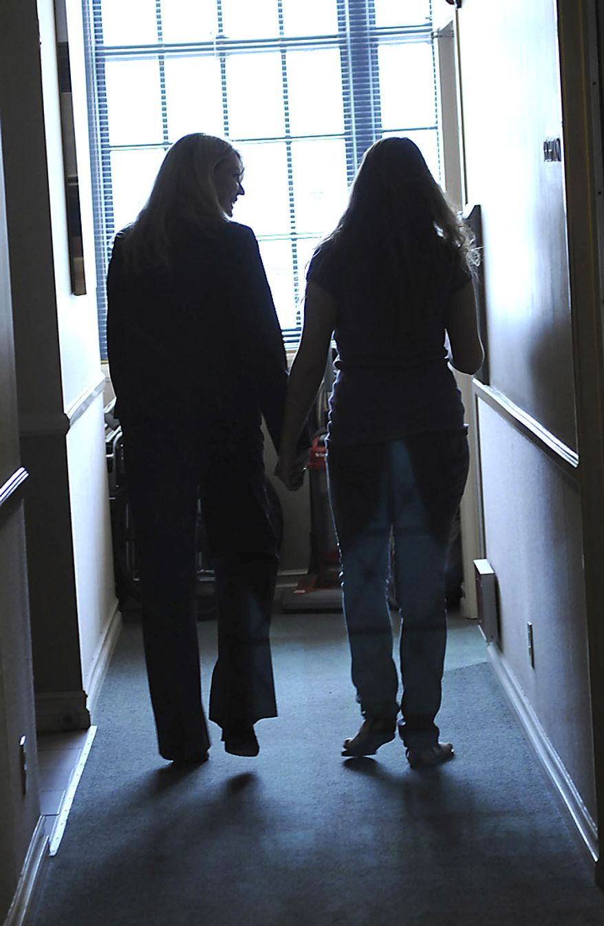 """Dr. Lois Lee holds hands with her student """"Jane""""  while walking together down a hallway after a therapy session at Children of the Night in Van Nuys, Calif., on April 21, 2011. """"Jane""""  was rescued off the streets of Portland, Oregon two years ago when she was just 15. """"This place has helped me so much. I was so different when I first got here,"""" """"Jane"""" said. She attends college classes now and wants to be a social worker where she can help people when she graduates.""""I just want to help people like Lois has helped me."""" (Garrett Cheen/Special to The Washington Times)"""