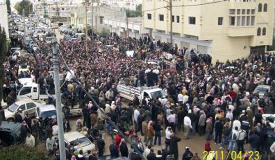 In this citizen journalism image made on a mobile phone and acquired by the AP, Syrian anti-government protesters march in a funeral procession for slain activists in Izraa, Syria, Saturday, April 23, 2011. (AP Photo)