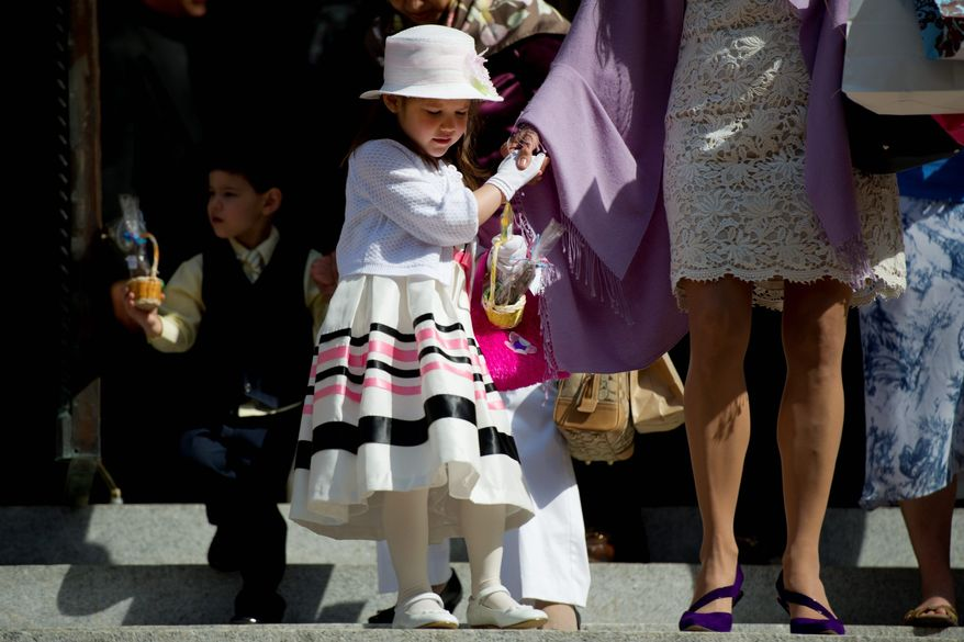 Wearing her Sunday best, 5-year-old Mercedes Webster walks down the church steps after Easter Mass at the historic Cathedral of St. Matthew the Apostle on Rhode Island Avenue in the District. The service, attended by an overflow congregation, focused largely on Scripture. (Drew Angerer/The Washington Times)