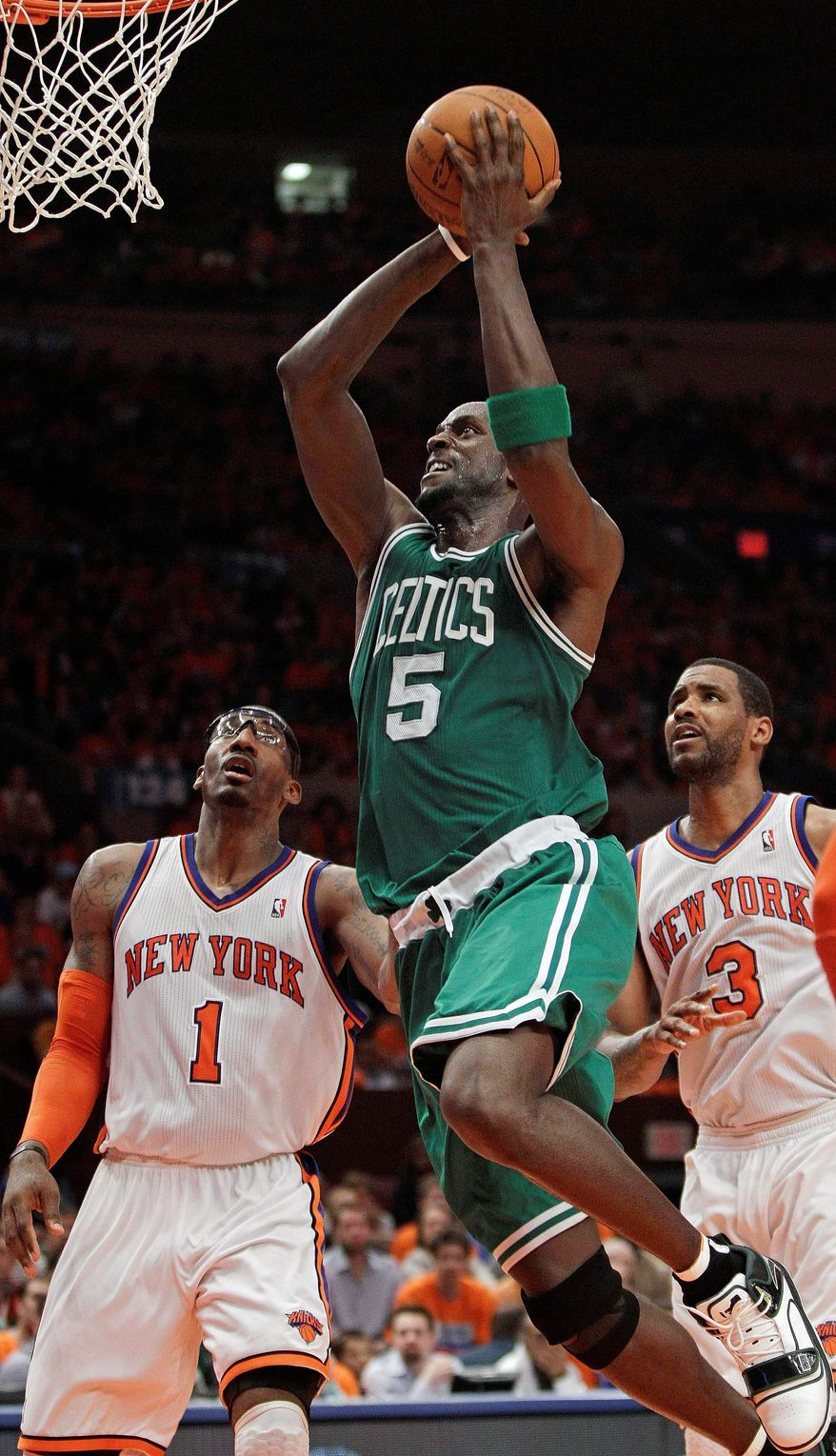 Boston forward Kevin Garnett splits New York forwards Amar'e Stoudemire (1) and Shawne Williams on a drive to the basket. Garnett totled 26 points and 10 rebounds in the Celtics' 101-89 win. (Associated Press)