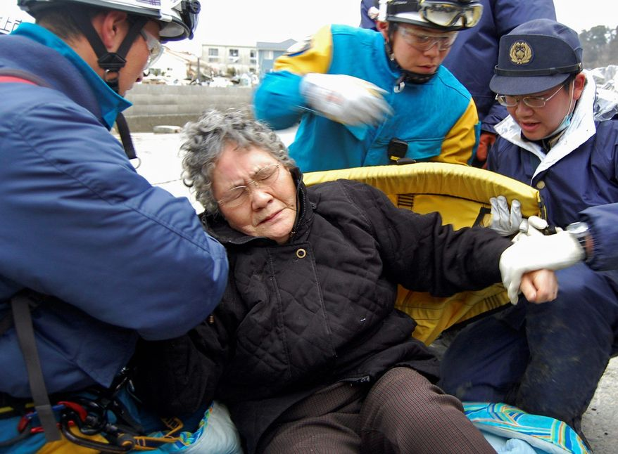 Sumi Abe, 80, is rescued from her tsunami-destroyed home in Ishinomaki, Japan, on March 20. Likely the most famous of the tsunami survivors, Mrs. Abe has come to personify the enduring spirit that many believe will help Japan overcome its worst crisis since World War II. (Asahi Shimbun via Associated Press)
