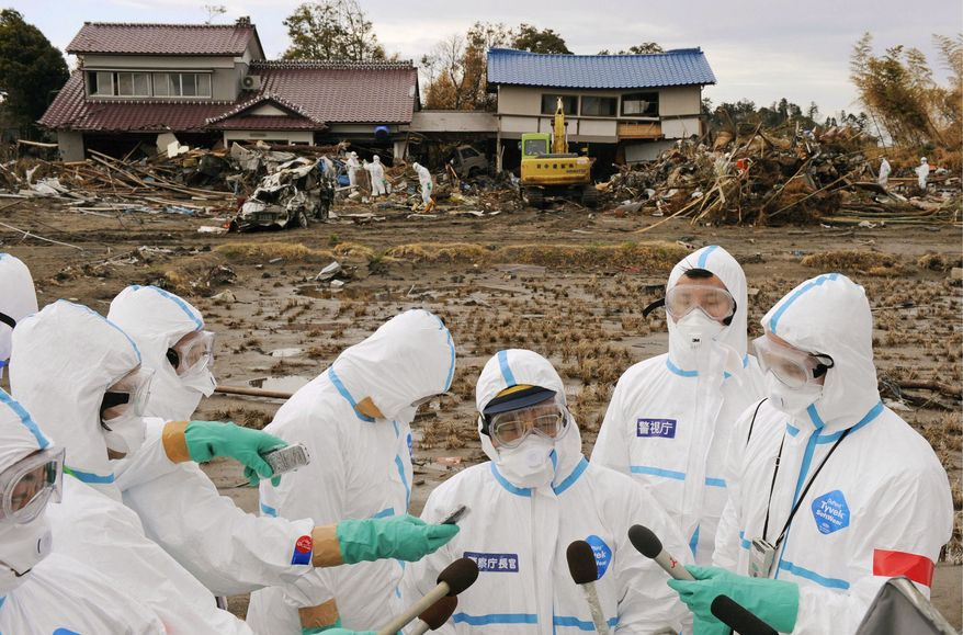 Reporters surround National Police Agency Chief Takaharu Ando (center) for news on the search effort in Futaba, a town now almost deserted near the radiation-spewing Fukushima Dai-ichi nuclear power plant in northeastern Japan. Soldiers joined the effort Monday to find the remains of some of the 11,900 people still missing since the tsunami hit March 11. (Kyodo News via Associated Press)