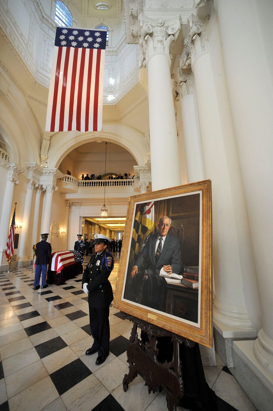 """Police officer Mia Hembrick on Monday stands next to William Donald Schaefer's portrait while the former governor and Baltimore mayor's casket rests at the State House in Annapolis. """"I'll remember him as a very dedicated, honest individual,"""" former Gov. Marvin Mandel said of Mr. Schaefer. (Associated Press)"""