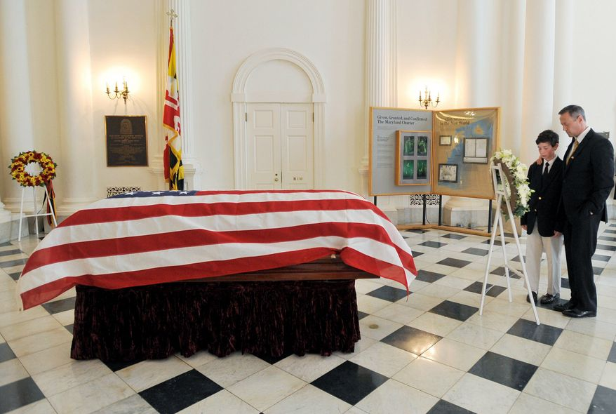 Gov. Martin O'Malley and his son, William, pay respects at the casket of longtime Maryland politician William Donald Schaefer in the State House in Annapolis. (Associated Press)