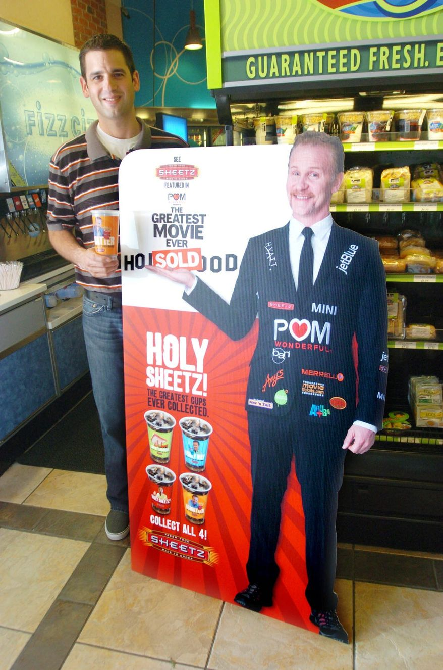 """ASSOCIATED PRESS Filmmaker Morgan Spurlock's image appears on Sheetz collector's cups as part of the promotion of the new documentary, """"POM Wonderful Presents: The Greatest Movie Ever Sold."""" The convenience store chain is a key sponsor of the film.ASSOCIATED PRESS Fred McConnell, the Sheetz director of brand development, poses with a cutout of filmmaker Morgan Spurlock at a Sheetz location in Altoona, Pa. The city is changing its name to """"POM Wonderful Presents: The Greatest Movie Ever Sold"""" as part of the marketing campaign for Mr. Spurlock's new documentary."""