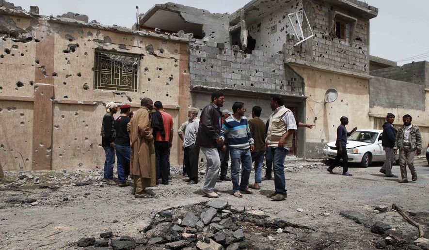 Neighbors examine damage to a house struck by a shell in Misrata, Libya, on Monday, April 25, 2011. Col. Moammar Gadhafi's troops, on the outskirts of the city, unleashed more shells, hitting a residential area and killing 10 people, including five members of one family, according to a doctor. (AP Photo)