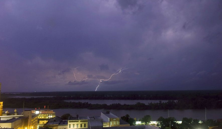 Lightning touches down on the Louisiana side of the Mississippi River early Wednesday before finding its way to Vicksburg, Miss., bringing heavy rain and winds with it. At least four deaths were reported in Mississippi. (AP Photo/The Vicksburg Post, Bryant Hawkins)